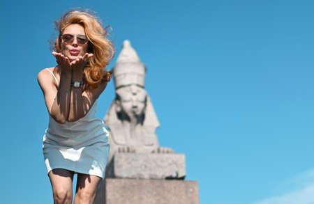 Young beautiful woman traveling Saint-Petersburg near ancient statue sphinx happy on blue sky background. Girl travel in Russia Stok Fotoğraf