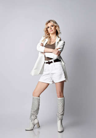 Gorgeous wealthy blonde woman in white shorts, jacket and summer high boots stands with arms crossed at chest