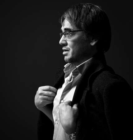 Black and white profile of adult man author, artist in white shirt and teed jacket on shoulders. Side view Stok Fotoğraf