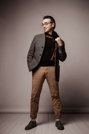 Optimistic smiling stylish adult man hipster in pants and plaid jacket stands taking off his scarf and looking aside