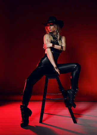 Cheeky blonde woman in black leather clothes pants, top and shoes and western stetson hat is sexual posing on stepladder