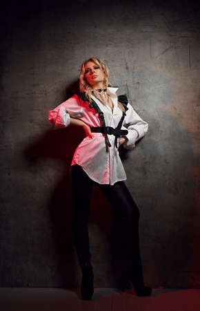 Insolent blonde woman mistress in leather pants, white shirt with leather belts and cap stands at concrete wall