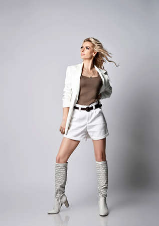 Gorgeous blonde woman in white shorts, jacket and high boots for summer stands looking at upper corner