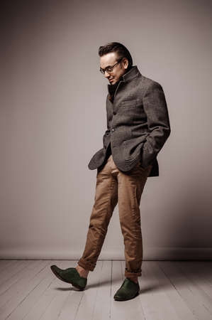 Smiling adult man in checkered jacket and black scarf stands with hands in pockets, looking down at his shoe Stok Fotoğraf