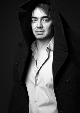 Black and white portrait of adult man poet, writer wearing white shirt and teed jacket coat on his head