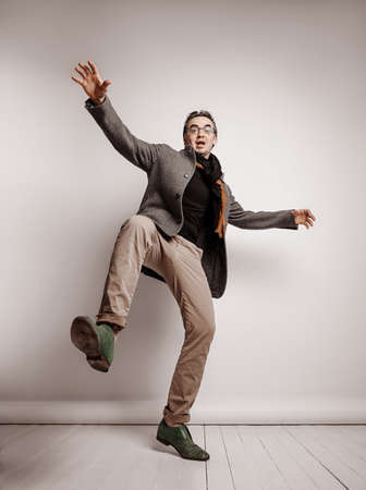 Adult man in pants and plaid jacket stands holding foot up, making giant step, falling down waving hands
