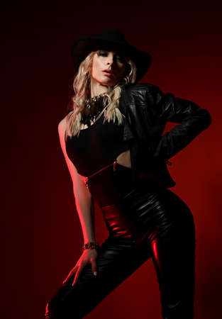 Excited blonde curly woman in black leather clothes pants, top, jacket and hat stands sexy posing, showing her buttocks