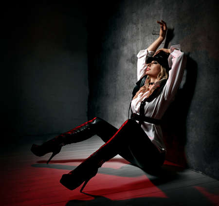 Sensual blonde woman in leather pants, white shirt and leather belts sits at concrete wall, hands up, feeling arousal