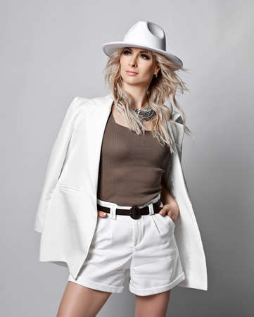 Sexy rich blonde woman in white wide-brimmed  hat, shorts and jacket on shoulders stands looking aside