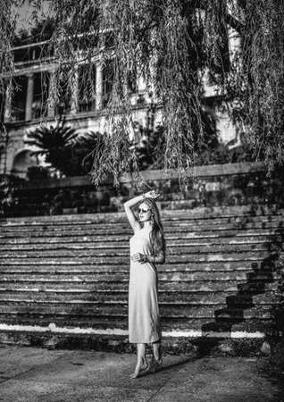 Black and white full-growth portrait of young slim woman tourist at stairs of ancient castle, palace