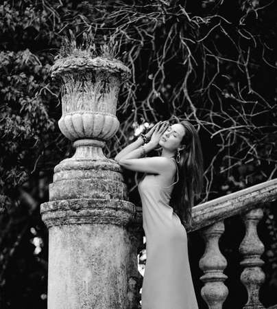 Black and white portrait of young slim sensual woman tourist at ancient stairs balustrade, stone flowerpot