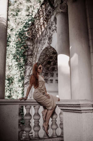 Young woman tourist in summer dress is sitting on ancient balustrade of old palace terrace looking at classic column