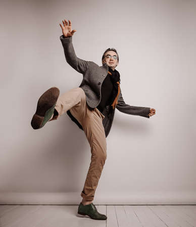 Stylish adult man hipster in pants and plaid jacket stands holding foot up, making giant step, falling down waving hands