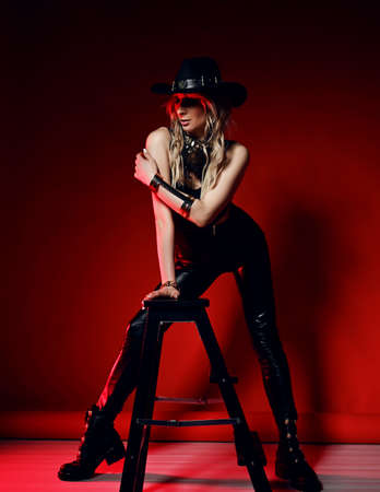 Impudent blonde woman in black leather pants, top and stetson hat stands posing at stepladder