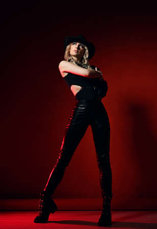 Slim blonde curly woman in black leather clothes shoes, pants, top and hat stands holding hand at shoulder looking aside Stok Fotoğraf
