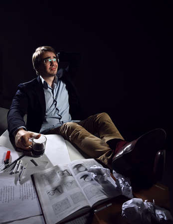 Middle-aged man in casual clothing and glasses sits at desk with his feet on table with book and papers, drinking tea Stok Fotoğraf