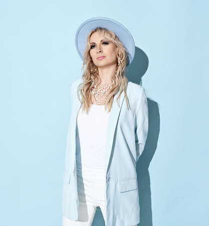 Wealthy blonde curly woman in white clothes jacket, pants and wide-brimmed hat standing holding hands behind her back Stok Fotoğraf