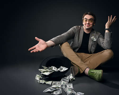 Happy smiling middle-aged man in jacket, jeans and shoes sits on floor by upside down hat full of dollars cash gesturing