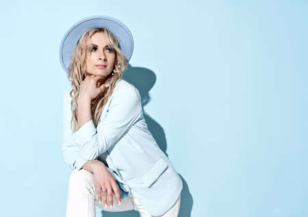 Wealthy blonde woman in white clothes jacket, pants and wide-brimmed hat standing with her foot up, leaning on knee Stok Fotoğraf