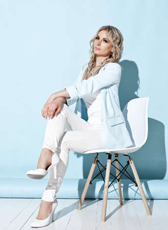 Gorgeous blonde curly woman in white blue pantsuit and high-heeled shoes sitting on stylish white chair