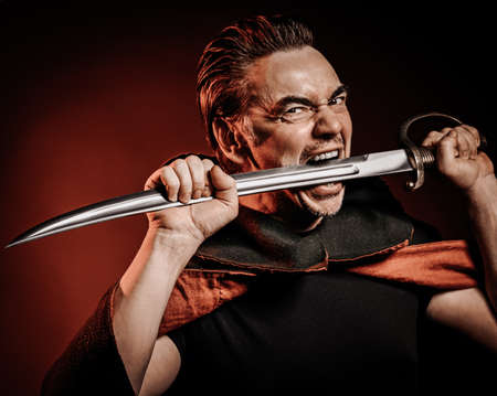 Portrait of strong courage fervor man warrior in cape holding sabre, sword in his mouth, ready to fight over red