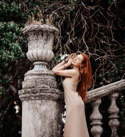 Portrait of young slim sensual woman tourist at ancient stone flowerpot on stairs balustrade handrail in old garden