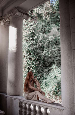 Young woman tourist in summer dress is sitting with her bare feet on ancient balustrade of old palace terrace, pavilion