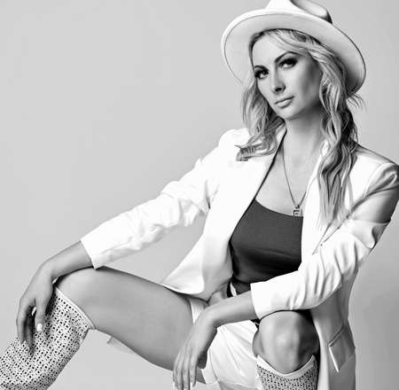 Beautiful pretty young blonde woman model in white stylish clothes, hat and high boots sitting and looking at camera Stok Fotoğraf