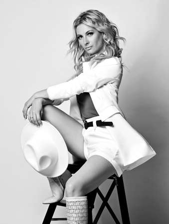 Beautiful pretty young blonde woman model in white stylish clothes and high boots sitting and looking at camera