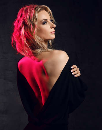 Beautiful pretty young blonde woman model in black dress with open back standing and looking away