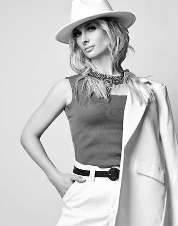 Beautiful pretty young blonde woman model in white stylish clothes, hat and accessories standing and looking at camera
