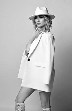 Beautiful pretty young blonde woman model in white stylish clothes jacket, hat and high boots standing and looking at camera Stok Fotoğraf