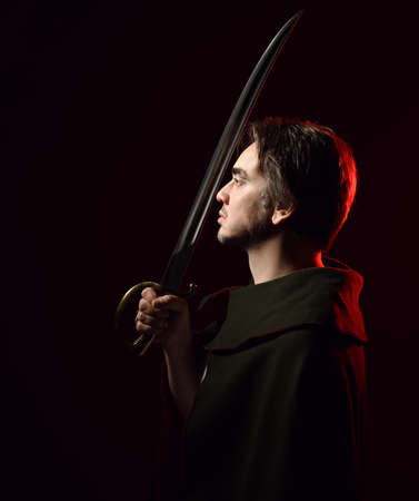 Profile, portrait of adult man warrior in cape standing sideways holding sabre, sword up in front of his face