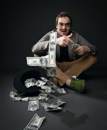 Rich insolent adult man in jacket, jeans and shoes sits on floor by upside down hat full of dollars throwing cash