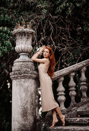 Young slim sensual barefooted woman tourist stands at ancient old stone flowerpot on stairs balustrade of old palace