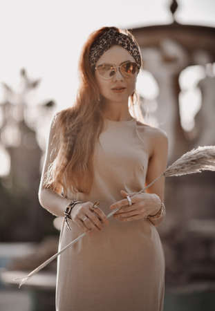 Young sexy gorgeous powerful redhead woman in sunglasses and summer dress stands at ancient fountain