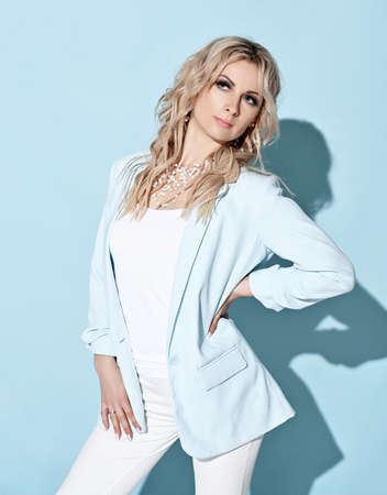 Gorgeous blonde curly woman in white blue jacket, tight pants, earrings and jewellery standing holding hand at her waist