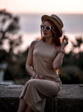 Gorgeous wealthy redhead woman at summer sunset sitting on stone parapet in sunglasses, straw hat and dress