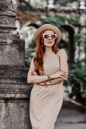 Stylish woman tourist in sunglasses, hat and summer dress stands at stone column in ancient palace garden