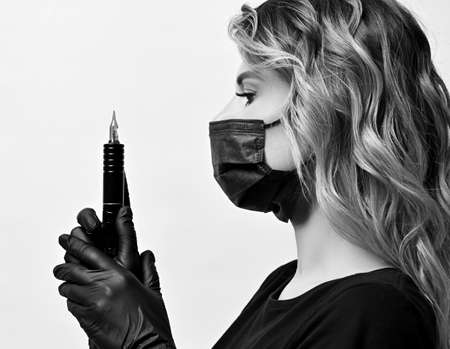 Black and white profile of curly woman in black protective medical mask and gloves holding permanent makeup machine Stok Fotoğraf