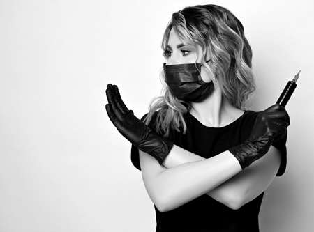 Black and white. Curly woman in protective medical mask and gloves with permanent makeup machine in hand gestures cross