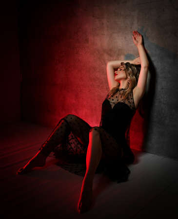 Excited young blonde curly woman in lace dress sits on floor at concrete wall in red spotlight glow, holding hands up Stok Fotoğraf