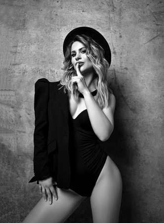 Black and white. Chic-looking flirty woman in bodysuit, jacket and hat stands at concrete wall gesturing secret sign