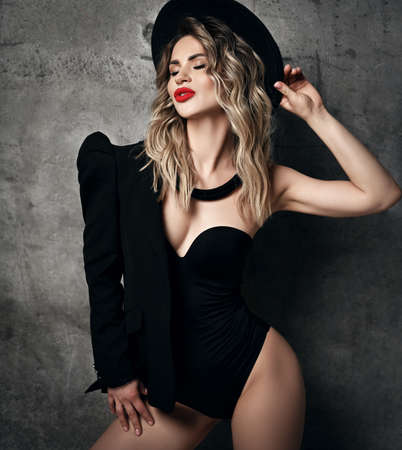 Chic-looking blonde curly woman with permanent makeup in bodysuit, jacket and hat stands at concrete wall blowing kiss