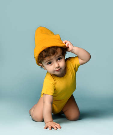 Small cute smiling curly baby boy toddler in yellow comfortable jumpsuit and hat crawling on floor