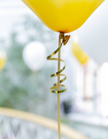 Yellow baloon with tape. Golden rope. Selective focus.