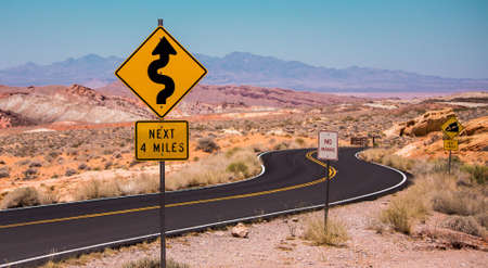 twisty: Road signs on a twisty road of Nevada desert and mountains Stock Photo