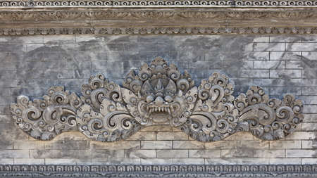 Traditional guard demon on the wall of the hindu temple. Bali. photo