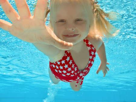 niños nadando: Feliz joven girl natación subacuática en piscina