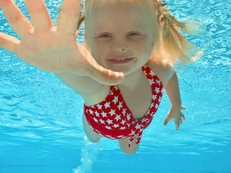 Happy young girl swimming underwater in pool